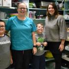 Photo shows two grade three students standing with two adults in a kitchen environment