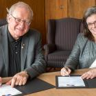 Two people sitting at a desk signing an official document