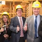 Five people standing side by side wearing hard hats and holding their thumbs up