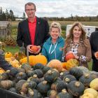 Photo shows a group of six people standing with a cart of pumpkins and gourds.