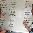 Photo shows two women talking in front of a whiteboard