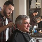 Minister Richard Brown is sitting in a barber chair having his haircut at The Humble Barber