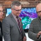 Minister MacDonald and  MP Sean Casey look at tablet heald by icejam founder Stu Duncan