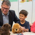 Photo shows two adults (including Minister Currie) sitting at a low table with two young boys holding stuffed animals.