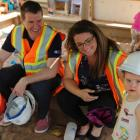 Minister Jordan Brown sits on the edge of a sandbox holding a hardhat, beside him sits Paige MacLaren, Director of the Morell Early Childhood Development Centre , and a cute little girl stands nearby.