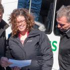 Three people in front of a transit bus looking at a document