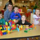 Minister Jordan Brown sits at a table with a group of day care children
