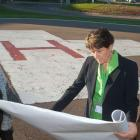 Minister Biggar and Minister henderson and one other person review construction plans near the PCH Helipad