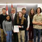 Minister Curries stands with a group of high school students