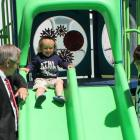 Dakota takes a slide on the new therapeutic playground while pediatric nurse manager Julie Smith and Health Minister Robert Henderson look on.