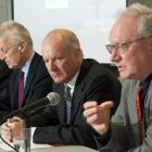 Premier MacLauchlan and three others sit at a table discussing the review