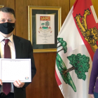 image of two people standing in an office with flags behind them
