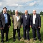 Four men standing shoulder to shoulder in a field