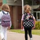three children walking toward a school