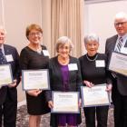Seven people standing shoulder to shoulder  holding certificates