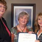Three women holding certificate for senior of the year award