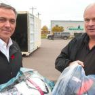Two men holding bags of textiles for recycling