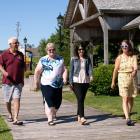image of four people walking on a wooden boardwalk