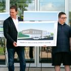 Four adults stand smiling as they look at a drawing of the new Tremploy facility to be built