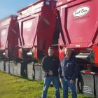 Harvey Stewart and Darrin Mitchell stand in front of a row of red-coloured Trout River Industries live bottom conveyor trailers