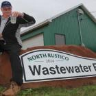 Les Standen holds a clear glass of Rustico's treated wastewater