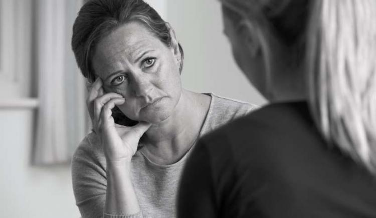 Black and white image of a forlorn female talking with another female.