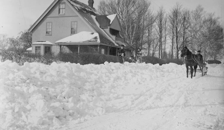 Horse and sleigh in front of house in winter, two children standing on snow bank looking at camera