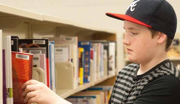 Un garçon prend un livre sur une étagère