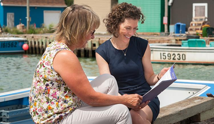 Two women sitting outdoors having a conversation and reading a booklet about Advance Care Planning.
