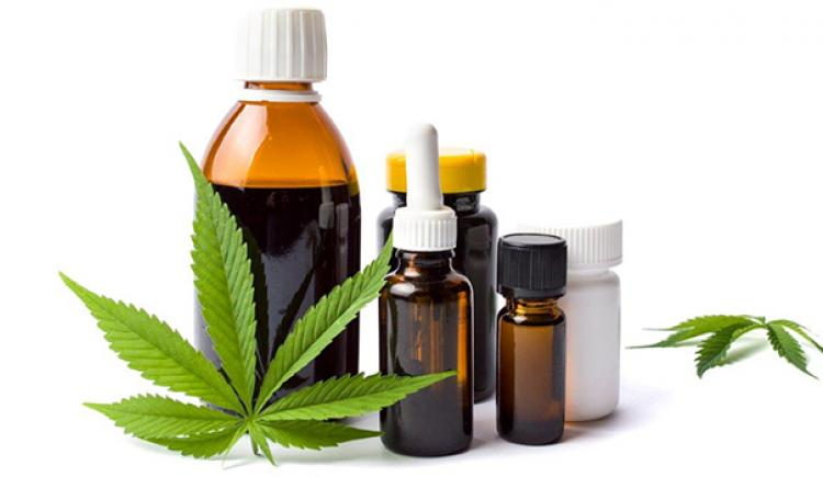 Various cannabis products pictured with a cannabis leaf in the foreground and background