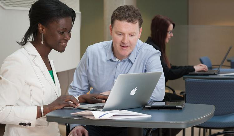 two people looking at a computer at a workstation