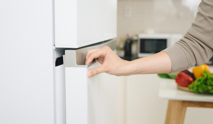 A hand opening a refrigerator.