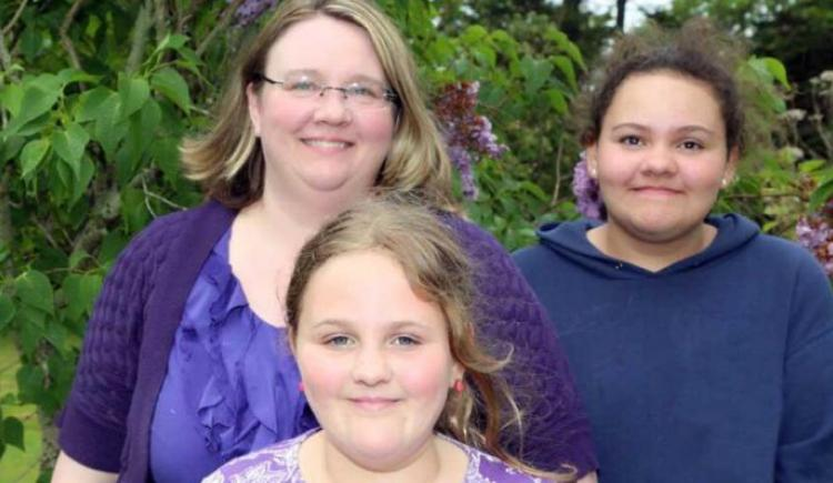 Mom and two female daughters dressed in purple smiling