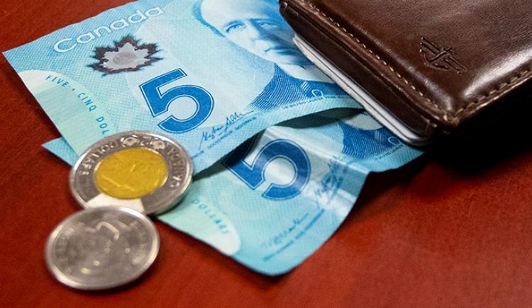 Image of $10 bill, loonie and quarter next to a wallet
