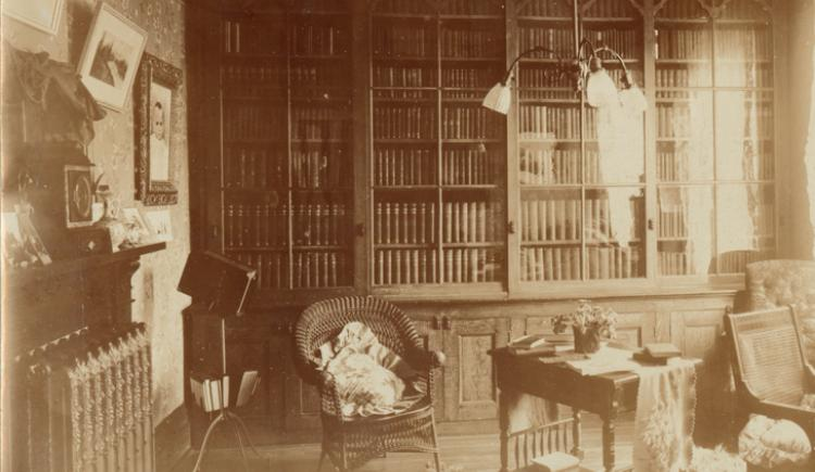 Photograph of an unidentified study or library room showing a wall lined with bookcases, [ca. 1890-1906]
