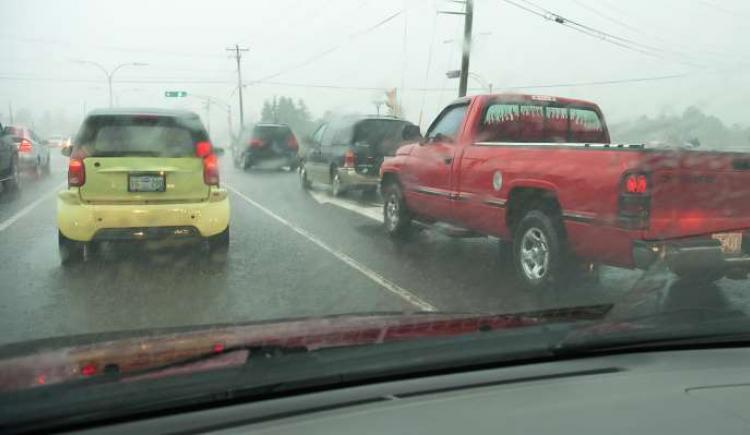 image through a car windsheild of traffic in rain storm