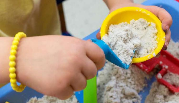 Image of a child's hand playing in a sand table