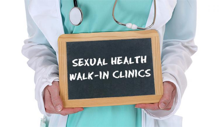 Health Care Professional holding a sign that says: Sexual Health Walk-in Clinics