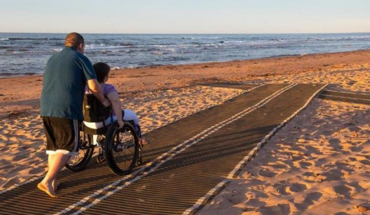 Individuals using accessibility mat on local beach