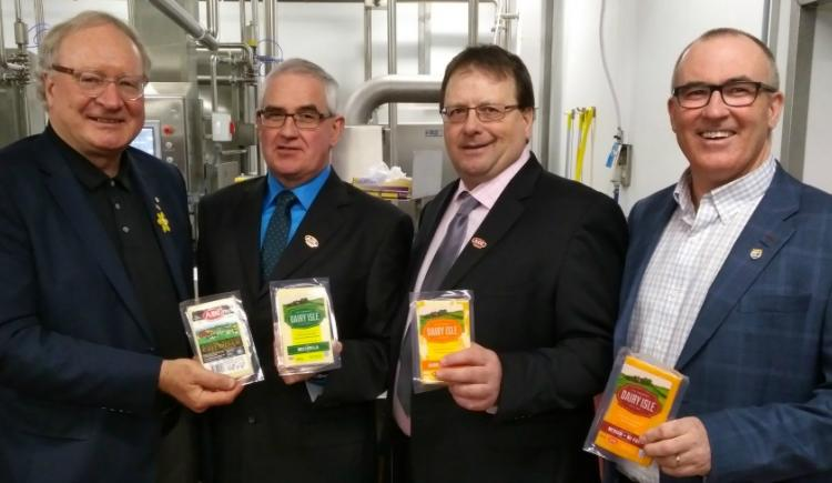 Photo shows four men holding packaged ADL cheese products