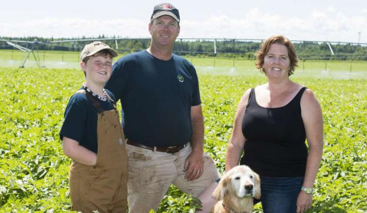 Jonathan and Katie MacLennan with son Gabriel and their dog stand in a potato field. Photo credit to Dan MacKinnon Photography