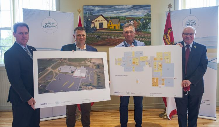 image of four people holding sketches of a future building