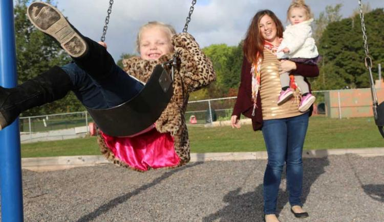 Alyse Rossiter pushes her daugher Akyvia on the swing outside her daycare