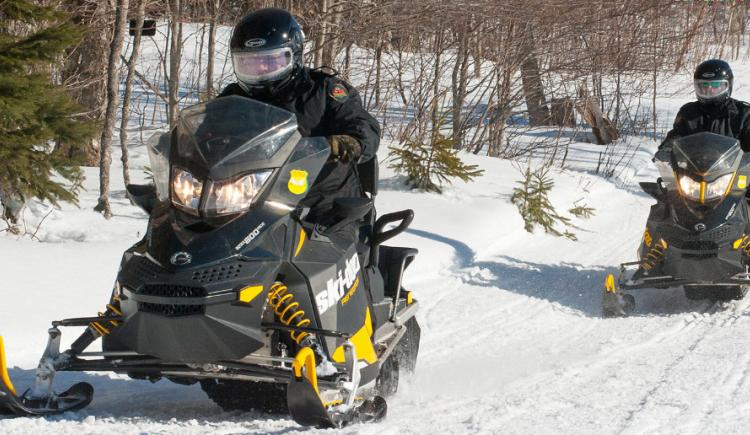 PEI's Conservation Officers patrolling on snowmobiles.