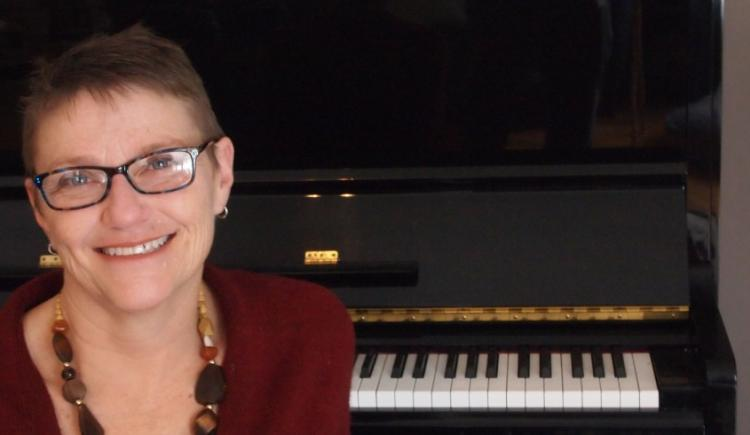 Dr. Janice Gillis sits at her piano