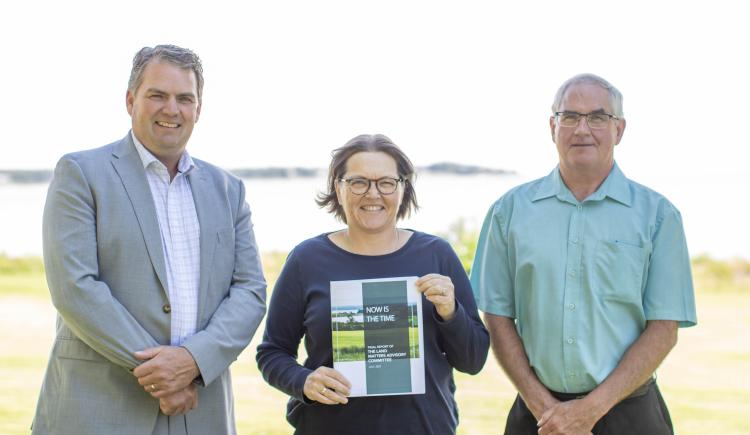 image of three people standing shoulder to shoulder and middle person holding the booklet report