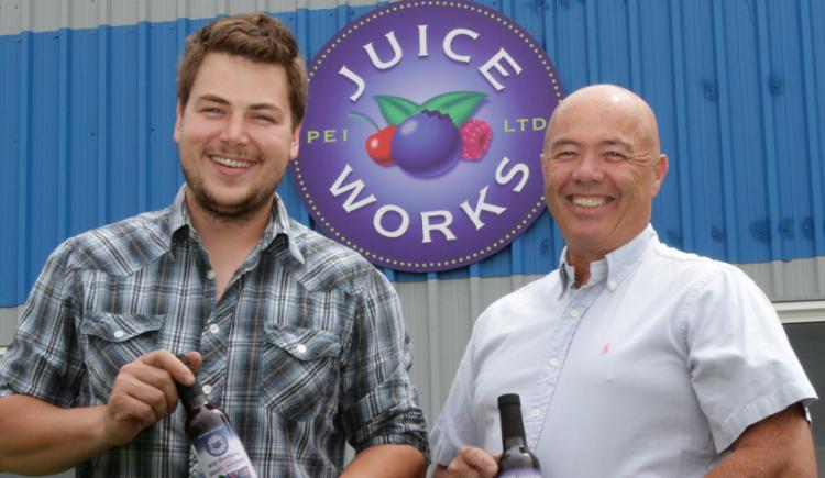 PEI Juice Works General Manager Jackson Platts, and President Denton Ellis hold bottles of the company's signature blueberry juice.