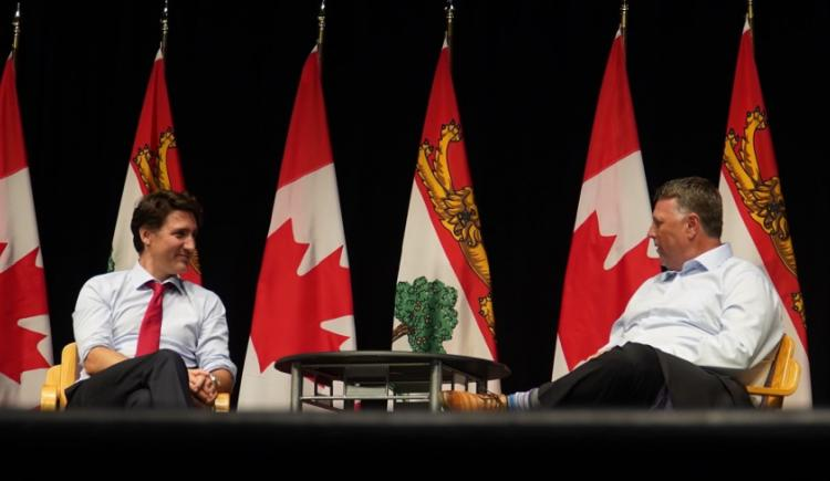 Premier Dennis King and Prime Minister Justin Trudeau sit in front of a row of Canadian flags chatting with each other.