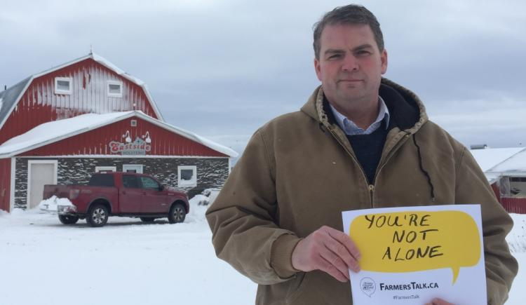 """Image of Minister Bloyce Thompson in front of his barn holding a Farmers Talk sign that reads """"You are not alone"""""""