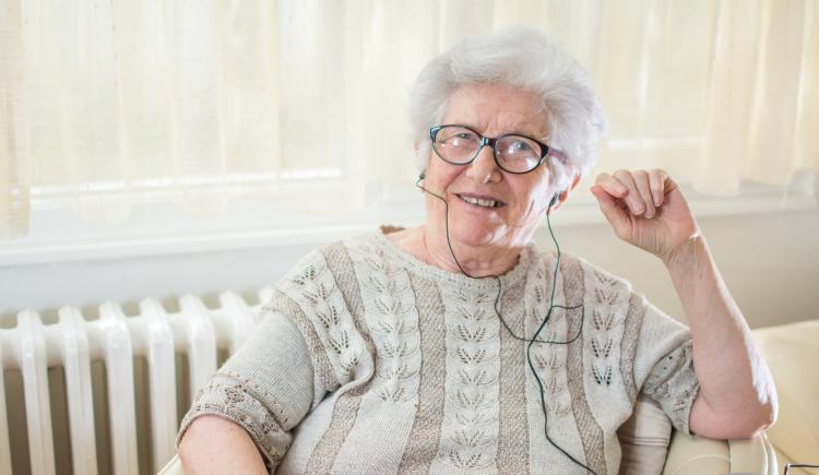 Female senior using headphones to listen to music device